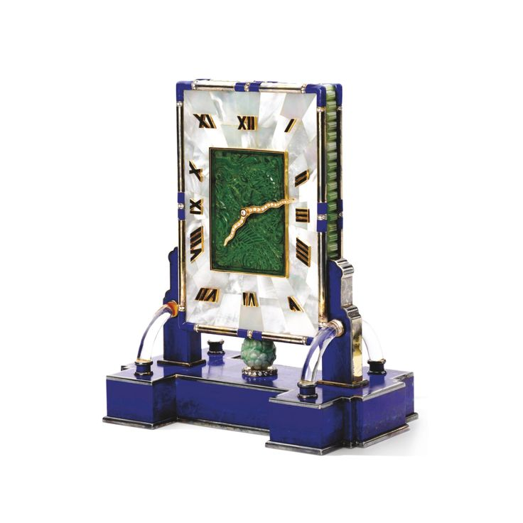 Jade, Gem Set and Diamond Timepiece, Cartier The rectangular case set with diamonds, lapis lazuli, green hardstones and mother-of-pearl, the dial centring upon a carved jade plaque surrounded by mother-of-pearl inlays, with diamond-set hands and bloodstone Roman numerals, to a lapis lazuli base with carved jade bead and diamond details, mounted in silver, quartz movement, signed Cartier, numbered, with French assay and maker's marks, measurements approximately 195 x 160 x 100mm, fitted case…