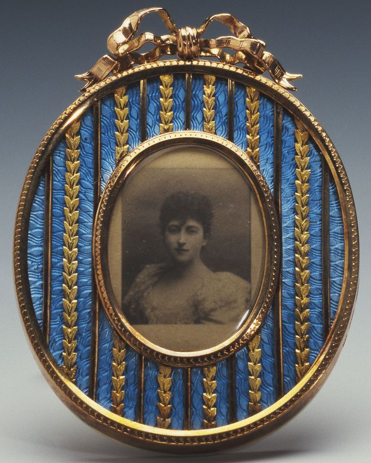 The third daughter of King Edward VII and Queen Alexandra, Princess Maud (1869–1938) married Prince Charles of Denmark in 1896. He became King Haakon VII of Norway in 1905. This photograph, taken in the late 1890s, is set into an oval gold frame by Fabergé, with blue guilloché enamel and alternate gold bands of laurel leaves surmounted by a ribbon cresting, workmaster Michael Perchin, c. 1895.