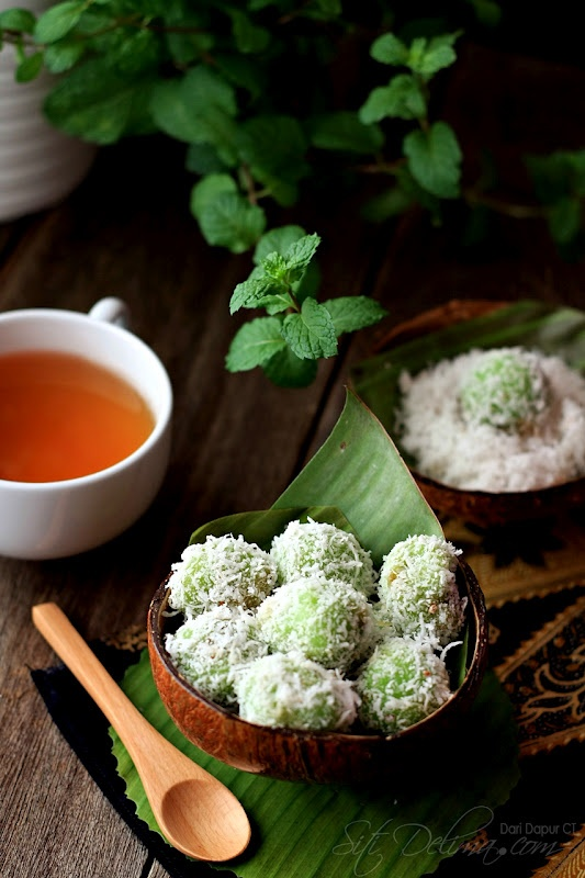 klepon , made with sticky rice flour , with melted gula jawa filling
