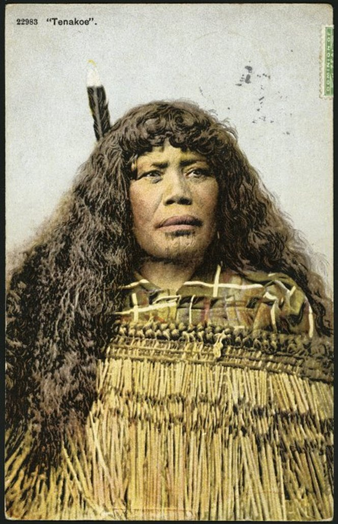 "New Zealand | ""Tenakeo""  Maori woman with long hair worn loose, chin moko, flax cloak and huia feather in her hair. ca. 1904 - 1914 