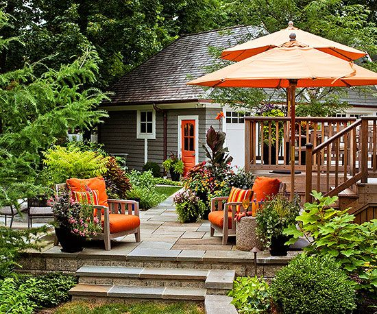 When you have a beautiful backyard, there's no need to go overboard with color. But sometimes a pop of color in small doses, like the orange used on this multi-level patio's chairs and umbrellas, is a nice touch.