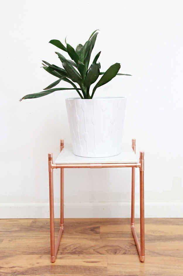 Posez un carreau de marbre sur un support en tuyaux de cuivre pour vos plantes.
