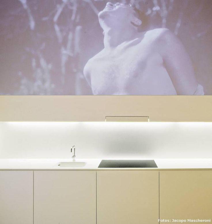 A lo largo de una inmaculada pared, sobre la cual se suele proyectar imágenes de video, se ha diseñado la #cocina que oculta sus electrodomésticos, al igual que los gabinetes superiores, escondidos detrás de este impecable plano vertical, pudiéndose acceder a los mismos por medio de un muy ingenioso sistema mecánico. #decoracion #minimalismo
