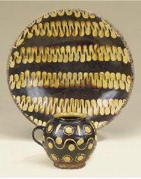 An English slipware bowl   Late 18th century   16½in. (42cm.) diameter   and a slipware handled jar -- 5½in. (14cm.) high (2)