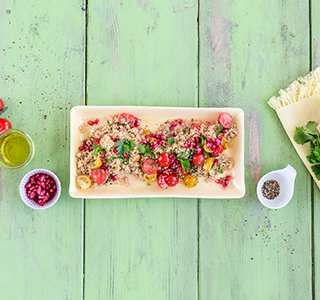 Veganer Quinoasalat mit bunten Tomaten und Granatapfelkernen
