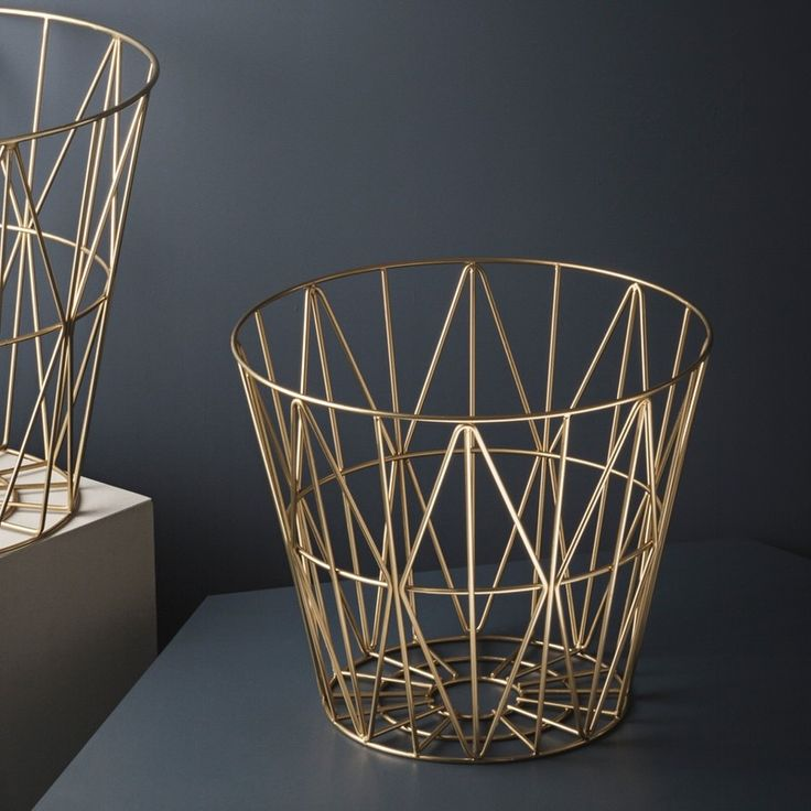 Ferm LIVING Wire basket medium Brass.The design and symmetry of these geometric triangles makes this brass wire basket is a modern design classic, we love this warm brass plated addition.  A stylish solution for storage or as a small table. Made from brass plated metal, this sturdy and practical basket can be a great solution for storing anything in the home from firewood, toys, magazines, towels & more. If you need a side table then add one of the gorgeous wooden tops  from Ferm LIVING a…