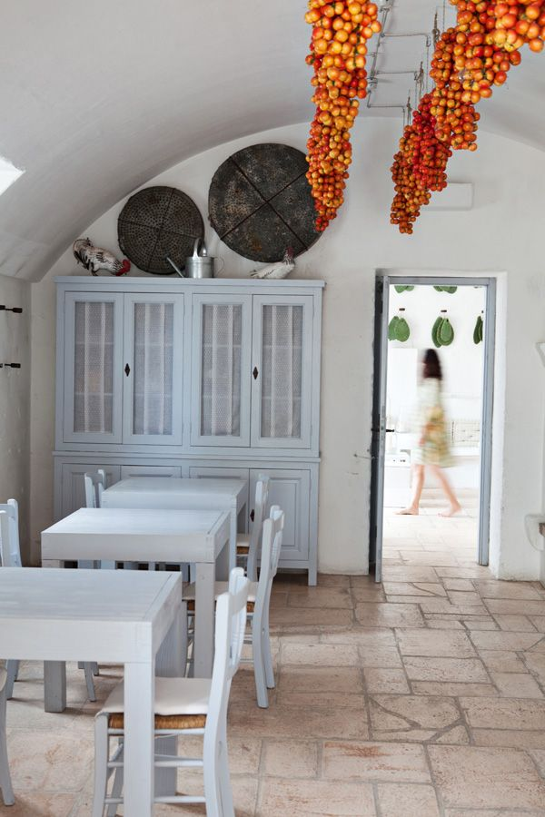 White dining room with bursts of orange and red. The beautiful Masseria Cimino - the venue for our Caravan Travel Photography Workshop
