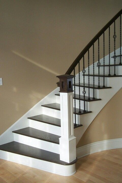 Simple wrought iron stair rails Could be a could way to transition from the white trim downstairs to the wood trim up stairs.