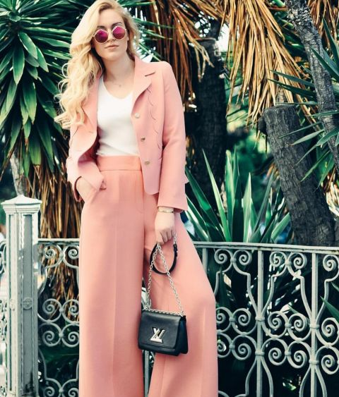 Reach for feminine suiting in a soft shade of pink—the color of the season. Keep your look tailored by opting for a pair of high-waisted pants and blazer, styled with a simple T-shirt and minimal accessories. @societygrl wearing ESCADA Toul Pants, $1,075, us.escada.com