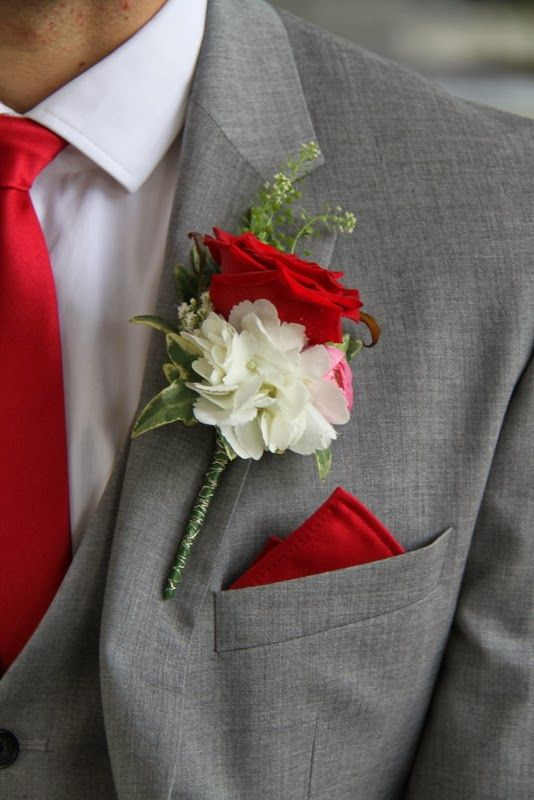 The Bride Groom's Boutonniere was designed to compliment his seriously red tie and included a beautiful Grand Prix Rose with Pink Ranunculas and Hydrangeas