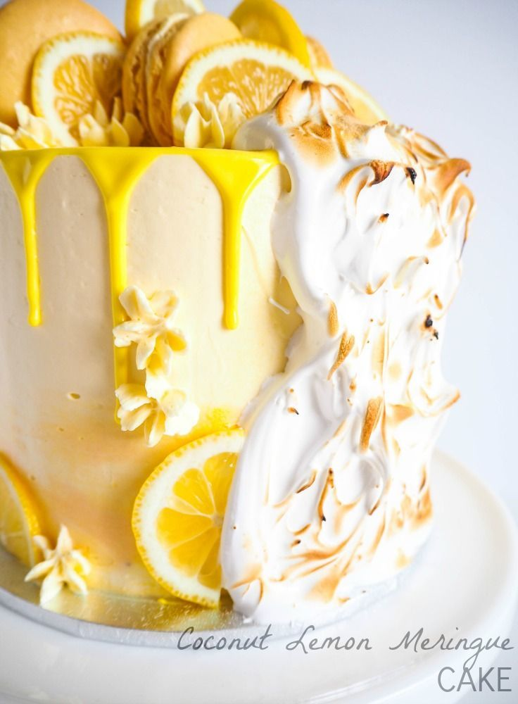 Coconut Lemon Meringue Cake - Moist and light coconut cake with tangy lemon curd, fluffy coconut lemon buttercream and pillows of cascading toasted meringue. All topped off by some cheeky lemon curd macarons.