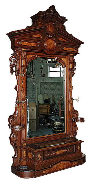 Beautifully carved antique Victorian hall piece executed in rosewood circa 1890. This majestic piece features a large beveled mirror, umbrella stands and coat hooks.