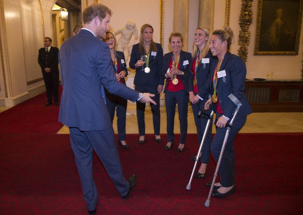 Prince Harry Photos Photos - Prince Harry speaks with Ladies Hockey Team with Susannah Townsend on crutches at a reception for Team GB's 2016 Olympic and Paralympic teams at Buckingham Palace October 18, 2016 in London, England. - Olympics & Paralympics Team GB - Rio 2016 Victory Parade