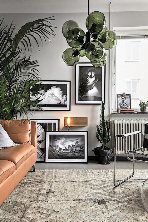 Masculine scandinavian interior. Green bubble lamp, black and white gallery wall, ethnic rug and camel leather couch with metallic elements.