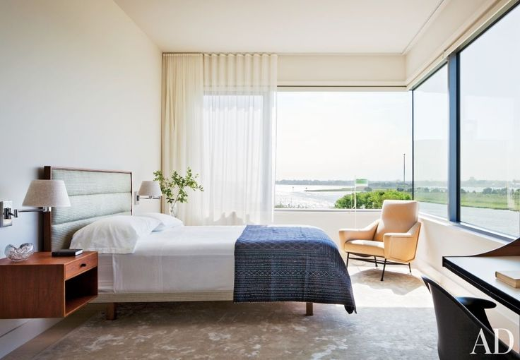 Sheer curtains filter the light in a modern Hamptons bedroom by Thad Hayes.