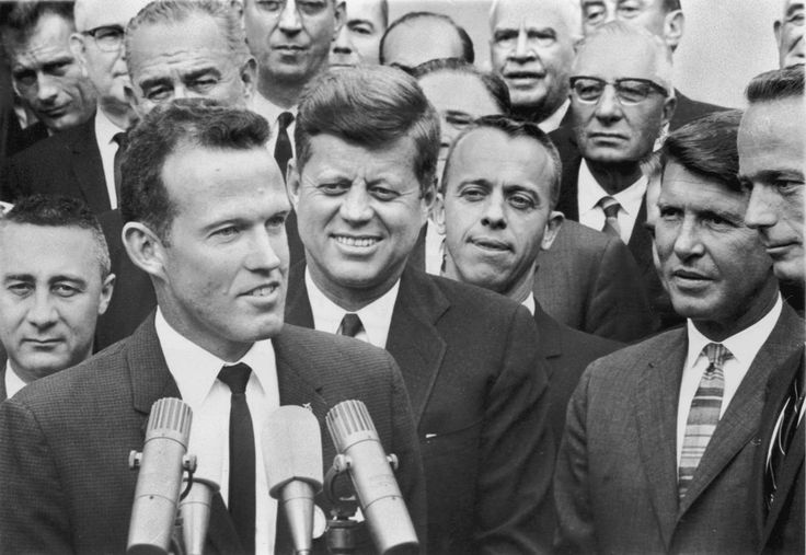 AMERICAN ASTRONAUT GORDON COOPER SPEAKS IN FRONT OF A MICROPHONE AS U.S. PRESIDENT J.F. KENNEDY (CENTER) AND (L-R) ASTRONAUTS GUS GRISSOM, ALAN SHEPARD, WALTER SCHIRRA AND SCOTT CARPENTER LOOK ON AFTER THE PRESIDENT'S MEDAL PRESENTATION TO THE FIRST AMERICAN ASTRONAUTS OF NASA'S MERCURY AND GEMINI SPACE MISSIONS