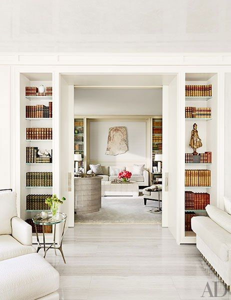 A view into the library, where a Bartolomeu Cid dos Santos stone relief is displayed above the sofa; the small table in the foreground is by Holly Hunt.
