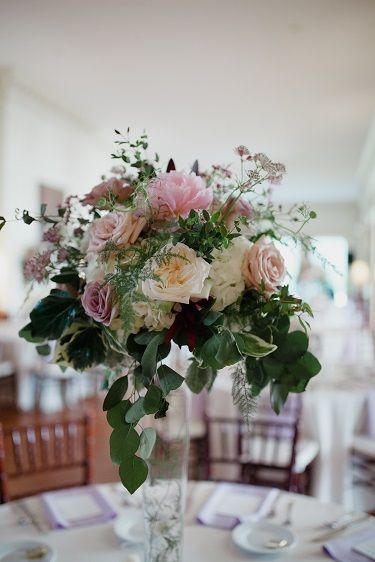 Floral centerpiece on tall pilsner vase with peonies roses chocolate lace astrantia and