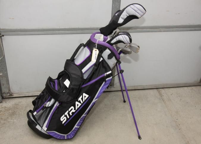 Strata women's golf club set incl pitching wedge, sand wedge, 6-9irons two having original plastic coating on heads, Strata plus putter, 5h Strata plus driver, 18° 5 Strata plus driver still in original plastic coating on head, and Strata plus titanium composite 460cc 1 driver, all in carrying case with colors black, purple, and grey with five zipper compartments, two mesh beverage holders, and tripod legs.