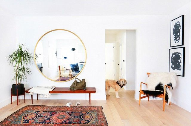 An oversize mirror in the entry area reflects the space's already abundant natural light.