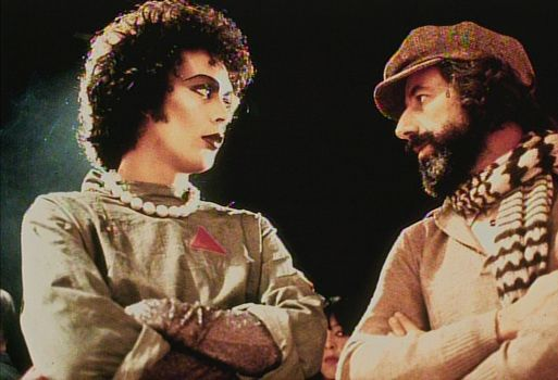 Tim Curry and producer Lou Adler are involved in a staredown.