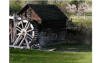 The Grist Mill is located beside Keremeos Creek, on Upper Bench Road just one kilometer east off Highway 3A on the north side of Keremeos.  Surrounded by the mountains in a near-desert environment, the Grist Mill and Gardens seems like an oasis with its shade trees, colourful flower beds and the waters of the creek flowing through the property.  Inside the store/house, now called the Exhibit building, there is a model of the mill and an area devoted to explaining the restoration process.