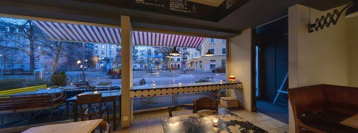 Piazza An warmen Abenden versetzt die Atmosphäre des Idaplatz im Kreis 3 einen in ein idyllisches Dörfchen in Italien. Hier wird gegessen, Schachbrettspiele werden ausgepackt, Boule wird gespielt und manch einer fühlt sich so inspiriert, dass er seine Schreibmaschine mitbringt – immer einsatzbereit. All das ist besonders gut von der Bar Piazza aus zu beobachten. Die herzige Einrichtung, weiss-rot karierte Tischdecken, erfrischende Getränke und das feine Essen laden zum Verweilen ein. Der…
