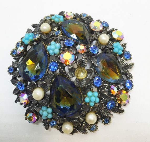 This is a beautiful signed ART © brooch from the 1960s featuring blue rhinestone, faux pearl, and metal intricately woven into a stunning