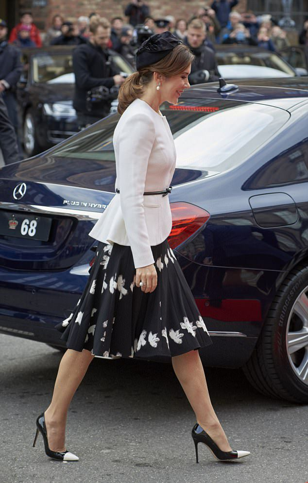 Crown Princess Mary of Denmark looked chic in a belted cream jacket teamed with a black A-line skirt and pointed heels, which she finished off with leather gloves and oversized pearl earrings. As she arrives to the Parliament to celebrate the Reformation's 500th anniversary in Copenhagen