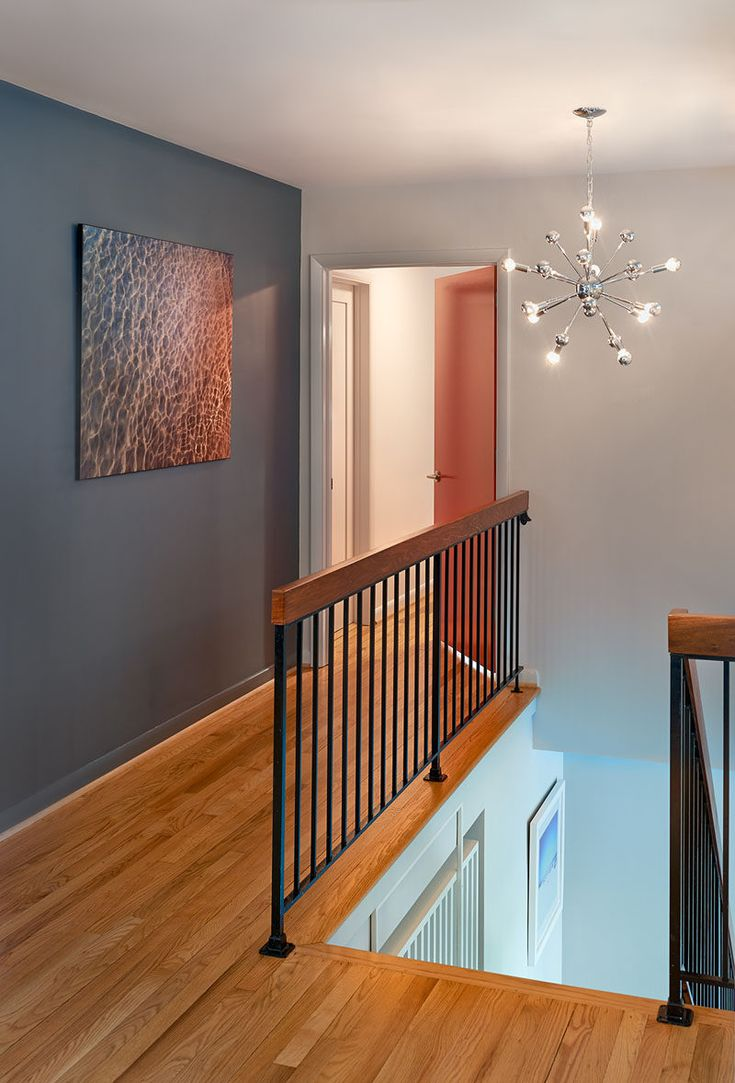 This Hallway Includes Hardwood Flooring A Dark Gray Accent Wall And Black Metal Railing Topped