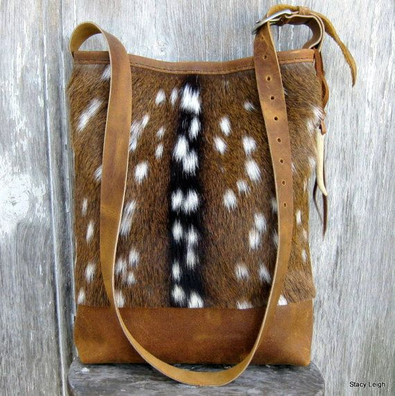 Cross body, distressed leather, and hair on, axis deerskin, bag. Hide was provided by customer.  Bag is 15 tall by 12 across with a 3.5 bottom. Hand stitched. Adjustable, leather, cross body strap. Fully lined with 2 leather pockets. Magnetic snap. White tail, deer antler tip embellishment is tied onto strap. Made for Jennifer.