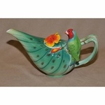 """Hand-painted tropical teapot with a red headed parrot. Measuring 10 1/4"""" long and 6"""" high, it holds 22 ounces. Features rich greens, oranges and reds.Dishwasher and microwave safe."""
