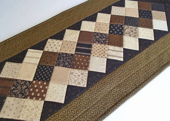 Civil War Reproduction fabrics in brown, black and tan are featured in this quilted table runner. The squares are set on point. This quilt would be at home in a country home, cabin or in a man cave - to protect your table or ad a pop of color. The setting triangles feature a rusty brown print on a black background. The brown and black print double fold binding was machine stitched on then hand stitched on to the deep gold backing. Machine quilted. Table runner 15 x 40. A nice size for a…