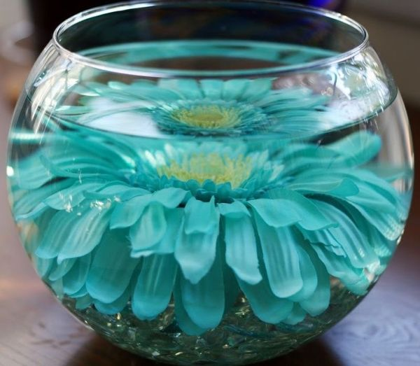 A fake flower submerged in a dollar store vase- because real centerpieces are expensive! Simple and pretty. Use your imagination, things in water always look beautiful and bigger!  How about those cut diamond crystals, seashells, starfish, bamboo stalk, pearls, butterflies, plastic figurines spray painted gold, silver or your wedding colors! destination wedding travel PJ by natalie.natty.noyes
