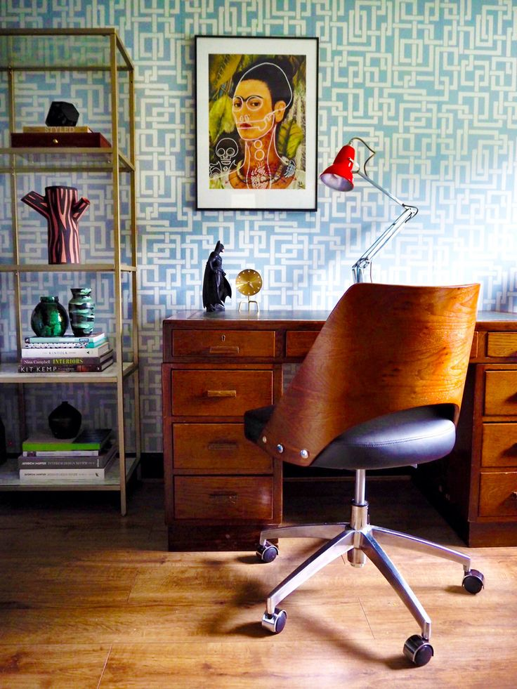 Home office decor and styling inspiration via Seasons in Colour and Amara Living. This room is featuring Farrow & Ball Enigma wallpaper and an Anglepoise lamp, the Vitra Desktop Tripod brass clock and the HAY tree trunk vase in pink. Chair from Made.com and bookcase styled with mid century vases.