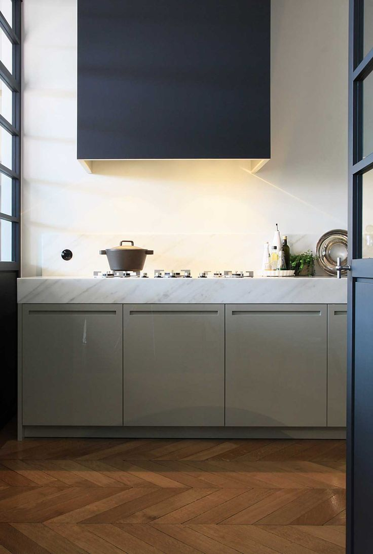 gray lower kitchen cabinets, thick marble counter, modern range hood, herringbone floors