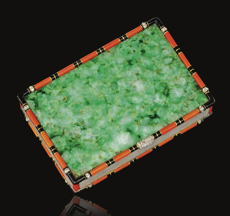 JADE, CORAL, MOTHER-OF-PEARL, ENAMEL AND DIAMOND COMPACT, CARTIER,  CIRCA 1925.  Of rectangular form, set with two bevelled jadeite panels, the sides decorated with mother-of-pearl engraved with a mosaic pattern, to a border of coral and black enamel highlighted with rose-cut diamonds, opening to reveal a powder compartment and a mirror,    signed Cartier, Paris, London, New York, Made in France and numbered, French assay marks, fitted case.  measurements approximately 90 x 62 x 18mm,