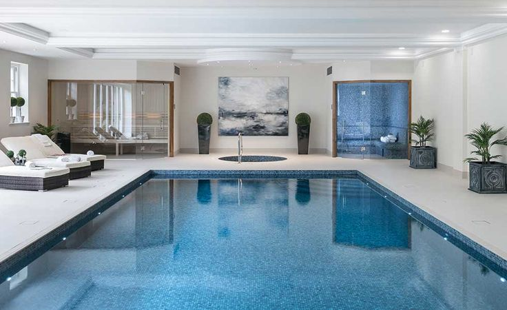 This indoor pool and spa, in Surrey, is mosaic lined and has an environmental dehumidification/heating system, automatic cover, automatic purification system, LED lighting, a tiled hot tub, steam room and sauna.