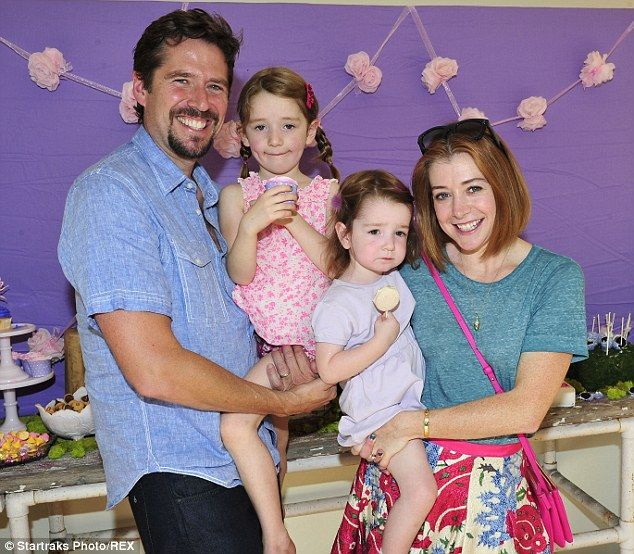 Happy family: Alexis Denisof held Satyana while Alyson Hannigan carried Keeva at the third birthday party of Tori Spelling and husband Dean McDermott's daughter Hattie on Sunday, 11 October 2014.