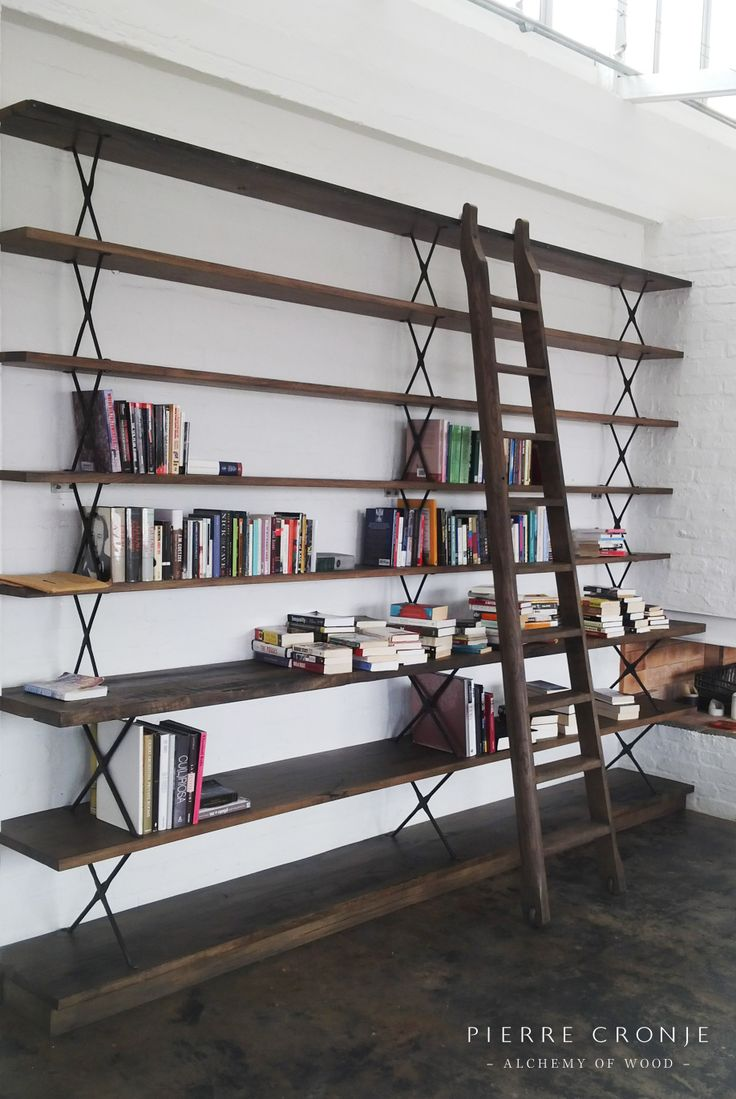 A Pierre Cronje custom shelving unit recently installed in a converted warehouse. The shelves and sliding ladder are made from local oak and the X-braces are wrought iron.