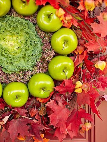 Farm-stand fresh wreath: A head of kale surrounded by faux apples, seedpods and leaves. More details and more ideas here: http://www.midwestliving.com/homes/seasonal-decorating/fall-door-decorating/?page=1,0#