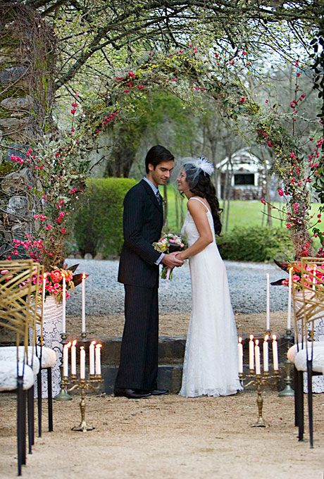 Brides: Romantic Candle and Floral Arch Decor. The ceremony area is decorated with candelabras and a floral arch. Instead of flowers use pinecones.