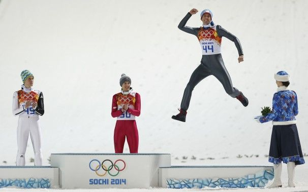 Norway\'s bronze medal winner Anders Bardal jumps onto the podium as Slovenia\'s silver medal winner Peter Prevc, left, and Poland\'s gold medal winner Kamil Stoch, center, applaud after the men\'s normal hill ski jumping final.