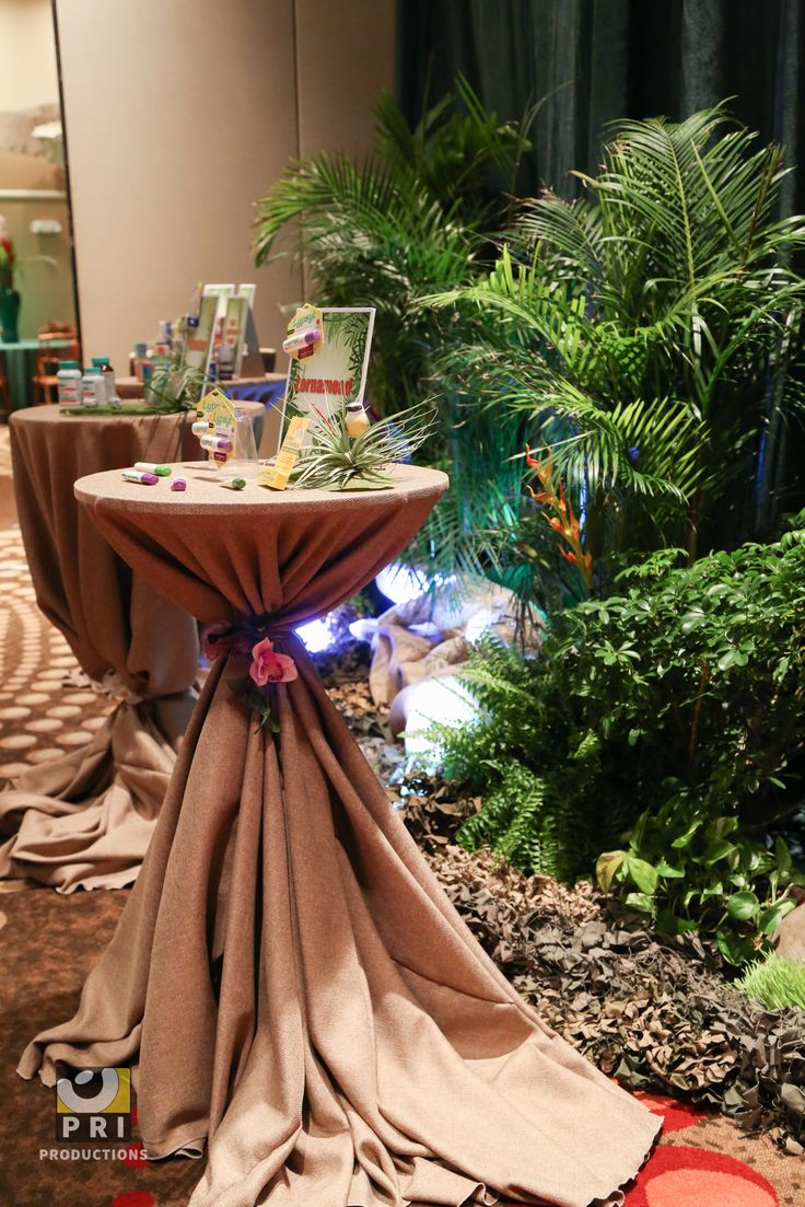 """""""It's a Jungle Out There"""" trade show. Love these burlap linens with the plants for this jungle themed event."""