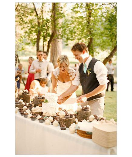 Tree trunks as cake stands...Newlyweds cutting cake at outdoor wedding reception