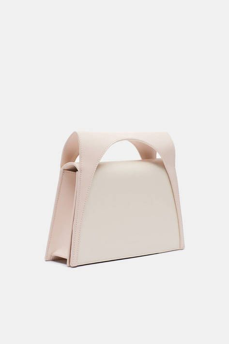 Elegant ingenuity and lunar inspiration give this bag its intriguing shape. Renowned for his inventive approach and effortless-looking results, J.W. Anderson has created a handbag that is deceptively simple. The top handle forms an attractive crescent-shaped cutout with the body, which opens not from above but with a magnetized folding flap. A removable shoulder strap offers the option of hands-free carrying, and an internal pocket keeps essentials close at hand.