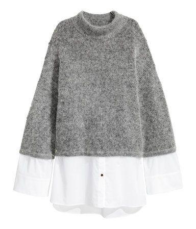 Beigemelert. En strikket, oversize genser i myk mohairblanding. Genseren har halvpolo og lange, vide ermer med lav skuldersøm. Vevd kant nederst og på