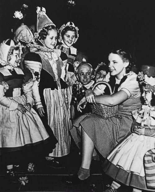 Judy Garland hangs out with the Munchkins while taking a break from filming the Wizard of Oz