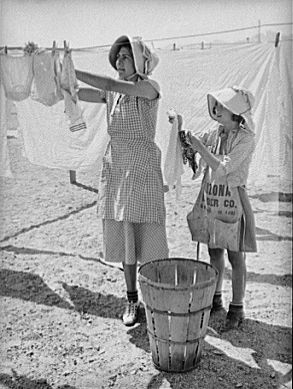 Wife of migratory agricultural laborer and daughter hanging up the wash at the Agua Fria migratory labor camp. Arizona. (May 1940)