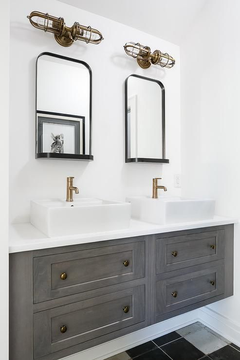 A beautiful gray floating bath vanity fitted with brass knobs and a white quartz countertop is finished with overmount sinks and brass faucets lit by aged brass caged sconces mounted above Restoration Hardware Astoria Mirrors with Trays.
